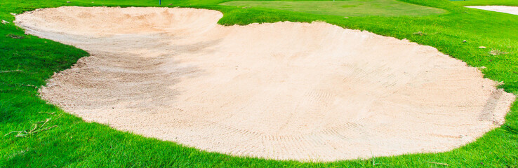 Sand bunker at the golf course and green grass