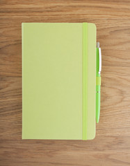 Green copybook with elastic band and pen on a wooden background.