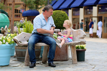 Father and little daughter relaxing on bench in outlet shopping