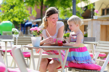 Mother and little daughter relaxing with drinks in outdoors cafe