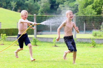 Two happy school boys playing in the garden with water hose