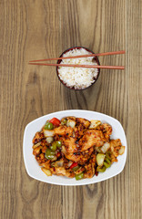 Chinese Spicy Chicken Dish with Rice in bowl on faded wood