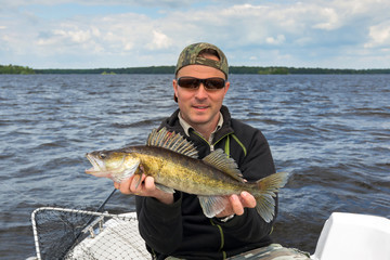 Happy angler with walleye trophy fish