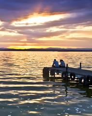 dos personas mirando la puesta de sol en el embarcadero del lago
