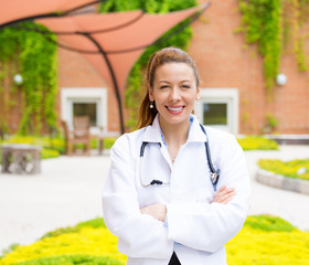 Happy smiling female doctor standing outside hospital