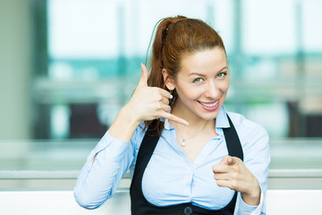 Woman giving call me sign, isolated corporate office background