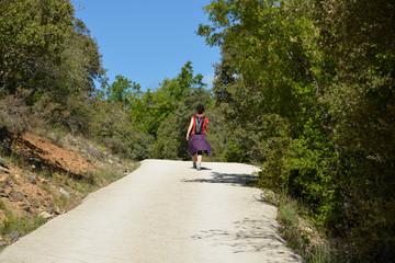 mujer caminando por un camino en el monte entre arboles