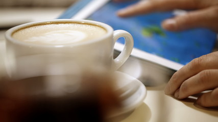 Woman using touch pad during coffee break