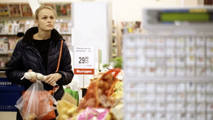 Young woman shopping in supermarket and choosing vegetables