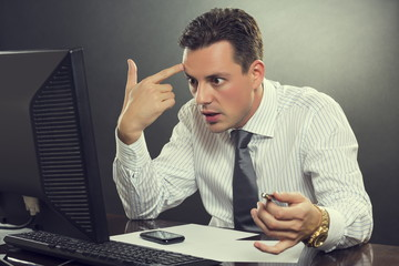 Desperate businessman pointing his finger to his head