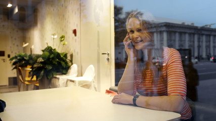 Evening phone talk of a young woman in cafe