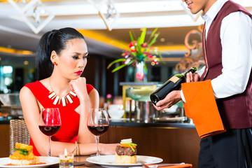 Waiter showing wine in Asian restaurant