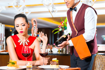 Waiter showing bottle of wine in Asian restaurant