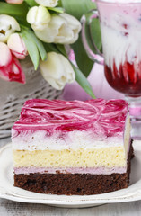Layer cake with pink icing. Cup of strawberry milkshake