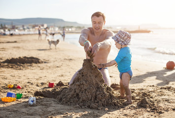 Father and son building a sand castle at the beach