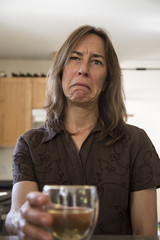 Unhappy Middle Aged Woman in the Kitchen Drinking Wine