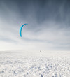 Kiteboarder with blue kite on the snow