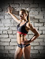 Muscular woman on brick wall background (dark version)