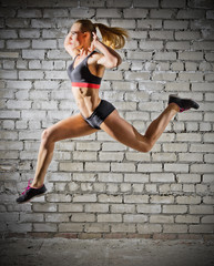 Muscular jumping woman on brick wall background (normal version)