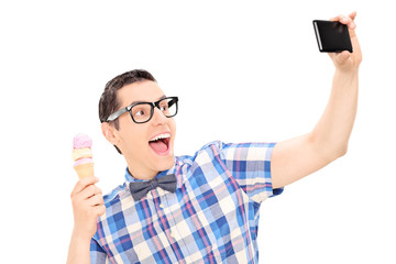 Excited man holding ice cream and taking selfie