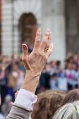 Frau hebt die Hand in der Menge