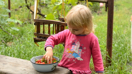 Cute Little Girl Eating Strawberry in Green Garden
