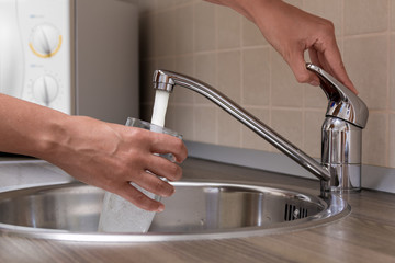 Woman, pouring water from faucet into a glass at a kitchen