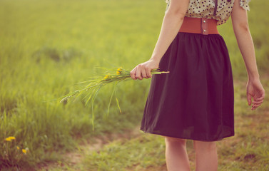 Background girl walking in a field in a dress and hold dandelion