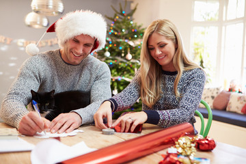 Couple Wrapping Christmas Gifts At Home