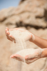 sand flows through the female hands