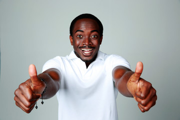 Smiling african man showing thumbs up on gray background