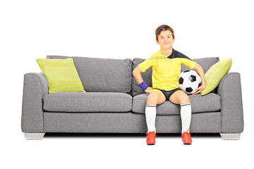Little kid sitting on couch and holding football