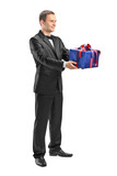 Full length portrait of a guy holding a present