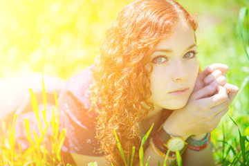 Beautiful redhead girl lay on grass. Soft focus on eyes.