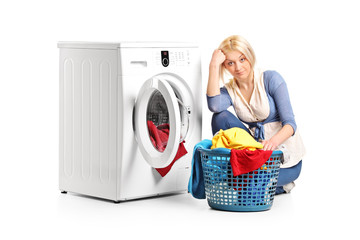 Bored woman sitting by a washing machine