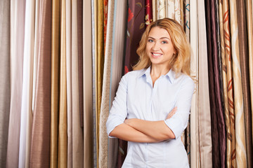 blond girl standing in fabric store.