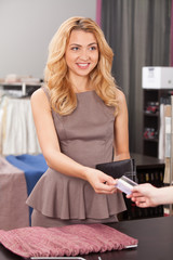 beautiful blond paying in store with card.