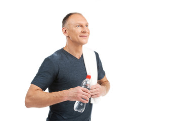 aged man holding water at gym.