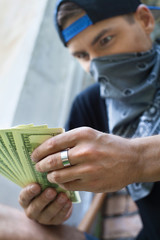 close up of criminal man holding money.