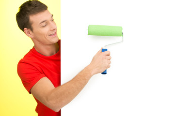 young man painting white wall.