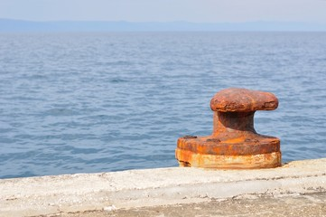 Old, rusty mooring bollard on port of Podgora, Croatia
