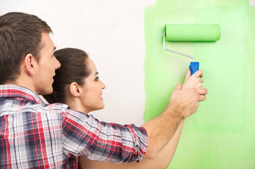 man helping woman paint wall.