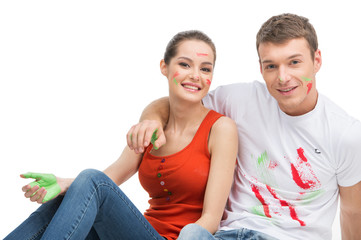 young couple sitting covered with paint.