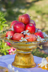 Red apple on a golden tray with pedestal.
