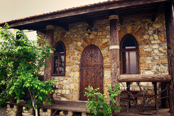 stone house with wooden arch doors and windows