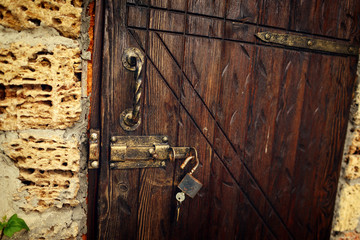 stone house wooden door with an iron padlock