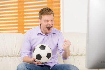 excited mature man watching football.