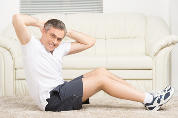 adult man doing sit ups on floor.