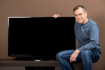older man sitting and holding tv set.