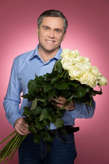 man holding rose bouquet and smiling.